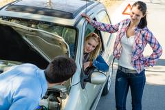 car defect man helping two female friends - stock photo