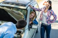 Stock Photo of car defect man helping two female friends
