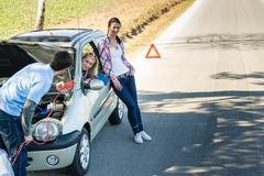Car defect man helping two female friends Stock Photos
