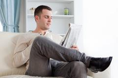 Stock Photo of Handsome man reading the news while having a coffee