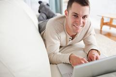 Stock Photo of Good looking man lying on a couch with a laptop