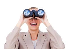 Joyful businesswoman predicting future success through binoculars Stock Photos