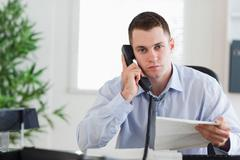 Stock Photo of Businessman on the phone with the author of a letter