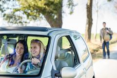 exciting girls drive car taking hitch-hiker - stock photo