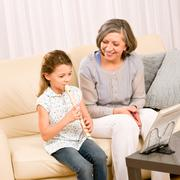 Stock Photo of grandmother teach young girl play flute happy