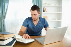 Student uses his laptop to work through his subject material - stock photo