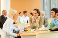 Stock Photo of cafeteria lunch young business people eat salad