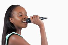 Smiling young woman singing into a microphone - stock photo