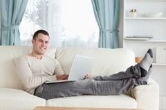 Stock Photo of Smiling man relaxing with a laptop
