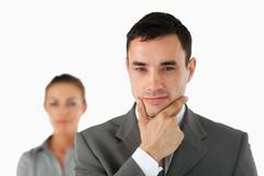 Close up of businessman in thoughts with colleague behind him - stock photo