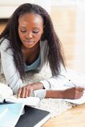 Close up of woman lying on the floor doing her homework - stock photo