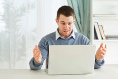 Businessman clueless about his laptop in his homeoffice Stock Photos