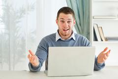 Businessman clueless about his notebook in his homeoffice - stock photo