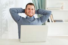 Smiling businessman leaning back - stock photo