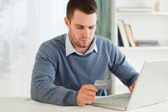 Male entering credit card information in his notebook - stock photo