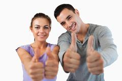 Young couple giving approval - stock photo