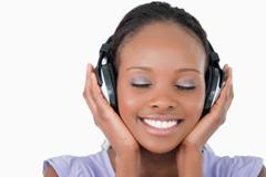 Close up of young woman listening to music with headphones on white background - stock photo