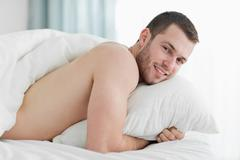 Stock Photo of Calm young man lying on his belly