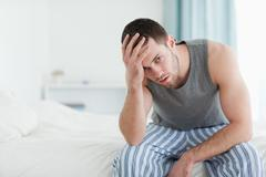 Tired man sitting on his bed - stock photo