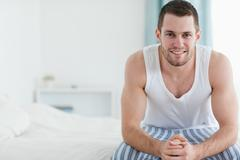 Happy man sitting on his bed Stock Photos