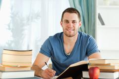 Stock Photo of Smiling student working on his book report