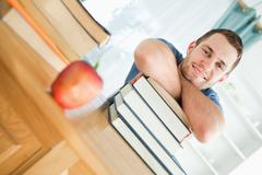 Smiling student with a pile of books Stock Photos