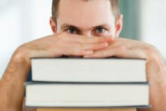 Stock Photo of Student hiding behind a pile of books