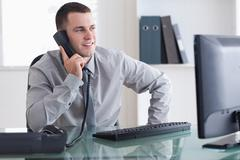 Businessman looking at the screen while on the phone - stock photo
