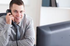 Businessman getting good news on the phone - stock photo