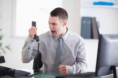 Businessman shouting at the phone - stock photo