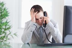 Stock Photo of Close up of businessman getting bad news on the phone