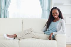 Woman sitting with legs on her sofa - stock photo
