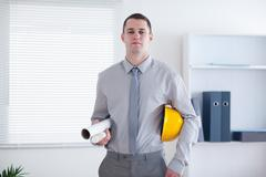 Architect carrying construction plans and helm - stock photo