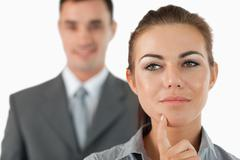 Stock Photo of Close up of thoughtful businesswoman with colleague behind her