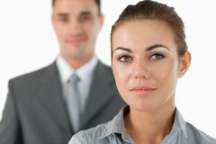 Stock Photo of Close up of young businesswoman with colleague behind her