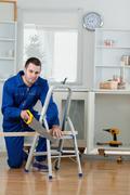 Portrait of a handyman cutting a wooden board Stock Photos