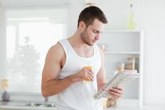 Stock Photo of Man drinking orange juice while reading the news