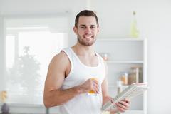 Handsome man drinking orange juice while reading the news - stock photo