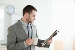 Stock Photo of Businessman drinking tea while reading the news