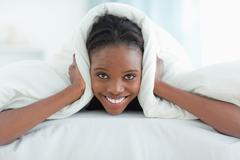 Smiling woman covering her ears with a duvet - stock photo