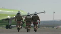 Firefighters walk along airfield - stock footage