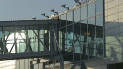 Passengers walk along a glass corridor to the airport Stock Footage