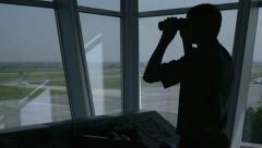 Airport Manager looks through binoculars from the tower Stock Footage