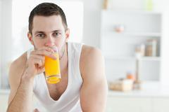 Good looking man drinking orange juice Stock Photos