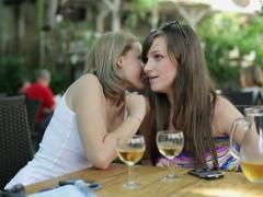 Woman talking secret to her friend in outdoor bar NTSC Stock Footage