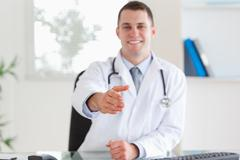 Smiling doctor welcoming patient - stock photo