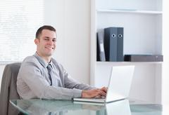 Satisfied businessman working on his laptop - stock photo