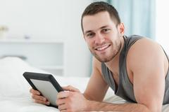 Stock Photo of Happy man using a tablet computer while lying on his belly