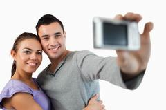 Stock Photo of Young couple taking photograph of themselves