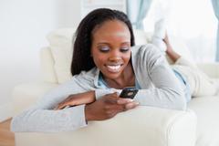 Woman reading text message on sofa - stock photo